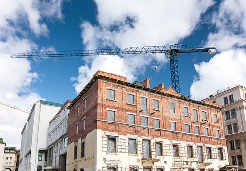 old brick building under reconstruction with building crane on blue sky background